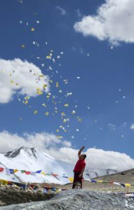 Man scattering buddhist prayer sheets at Tangangla pass on the way to Leh Kalachakra festival in july 2014